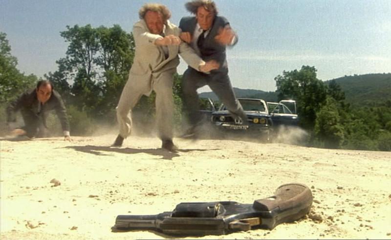 на фото: двое мужчин в прыжке, один на карачках  и револьвер в позиции лежа