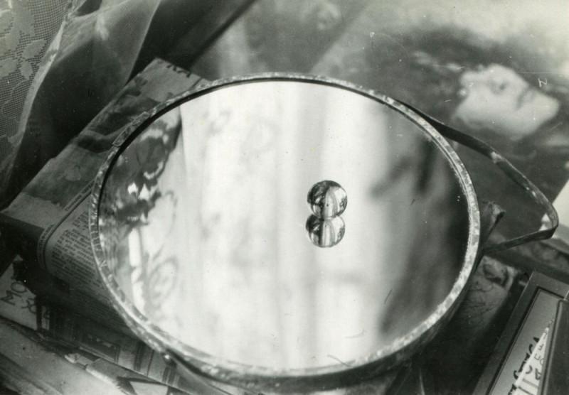 стеклянный шарик на зеркале, зеркало на книге, книга на столе, под стеклом постер А.Б,Пугачевой