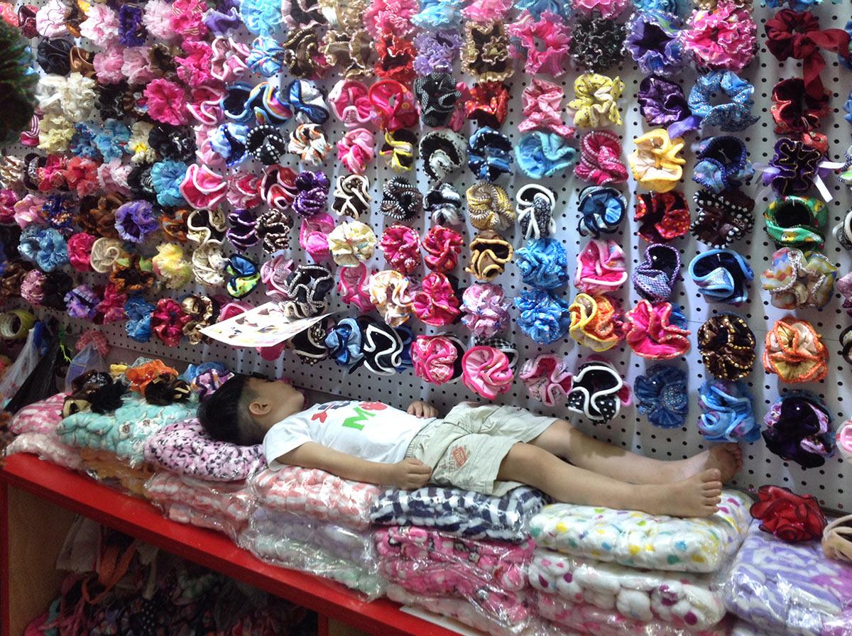 ребенок спит на резинках для волос. Город Иу, рынок Футьен