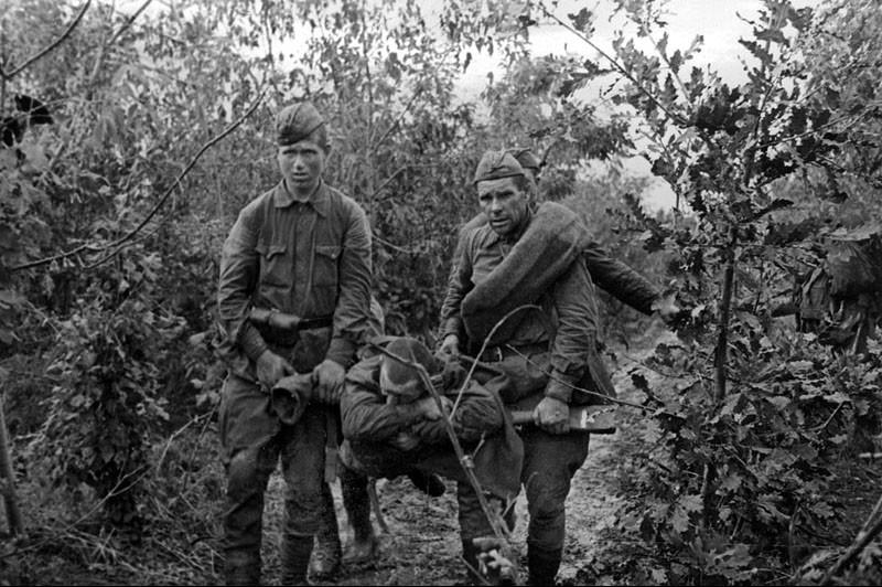 Бойцы несут раненого товарища