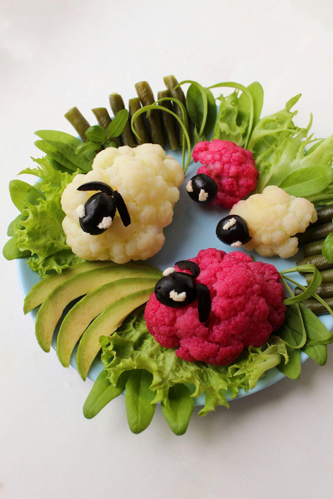 Вариант сервировки такого обычного овоща как цветная капуста для праздника или чтобы порадовать/привлечь к поеданию овощей ваших деток. Уверена, милые барашки не оставят равнодушным ни одного малоежку! Специально для #вкусныйавгуст я делюсь идеей, как раскрасить ваших барашков в яркий розовый цвет. Я отварила на пару 150г цветной капусты, предварительно разделив на самые привлекательные и устойчивые соцветия. Для покраски я просто натерла свежую свеклу и отжала через марлю, получив много полезнейшего и ярчайшего сока, обмакнула в сок готовые соцветия и получила маму и дочь барашков.Для мордочек и ушек я взяла черные оливки без косточек, использовала капусту для декора глаз. Стручковая фасоль, авокадо, салат и молодой шпинат послужили имитацией загона и зеленых полей.
