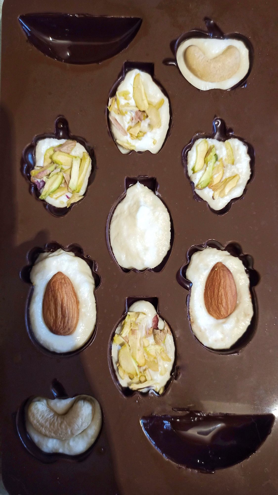 Для молочной начинки 30г сухого молока соединить с кокосовым молоком до консистенции сметаны, выложить на застывший шоколад вместе с рубленными орешками, сверху залить слоем шоколада