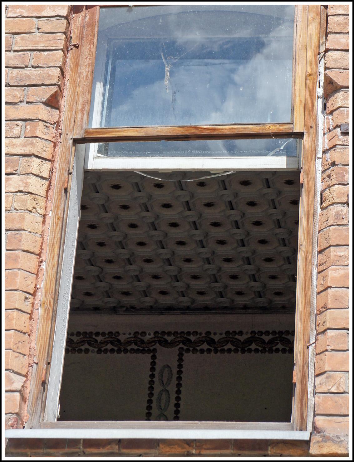 заглянув в окно, можно увидеь сохранившиеся детали богатого интеоьера