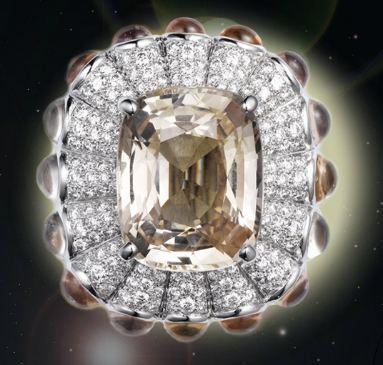 Ring, platinum, one 11.70-carat light orange sapphire, cabochon-cut light orange sapphires, brilliant-cut diamonds.