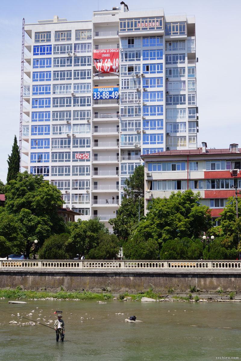 Ловля рыбы на фоне объявлений о продаже квартир