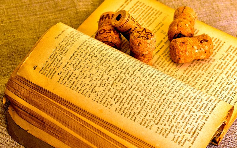 старая книга столетней давности и пробки от 50 летнего вина