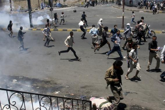 Anti-Houthi protesters seek refuge as pro-Houthi police troopers use tear gas to disperse them in Yemen's southwestern city of Taiz March 25, 2015