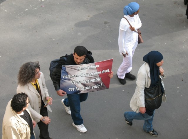 """Un de manifestants. On iscrit sur le placard: """"Si ma religion c'est mon choi[ et mon droit, Vivre ensemble et la seule voie!"""""""
