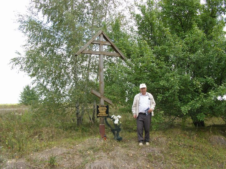 Павел Иванович Усов у памятного креста на братской могиле возле Полибино.