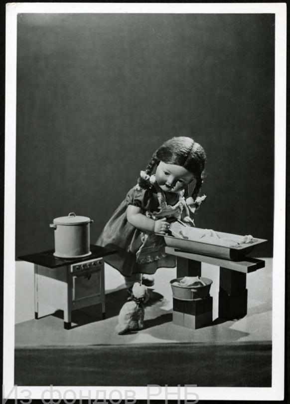 """Гершман М. М. [Кукла-девочка c игрушечными корытом и стиральной доской рядом с игрушечной плитой] : открытое письмо / фото М. Гершмана. - Ленинград : Госфотокомбинат """"Ленфотохудожник"""", 1958. - 1 л. : фотография"""