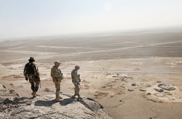 Two American soldiers and a member of the Afghan military looked for caves with weapons caches near Kandahar in February. Scott Olson/Getty Images