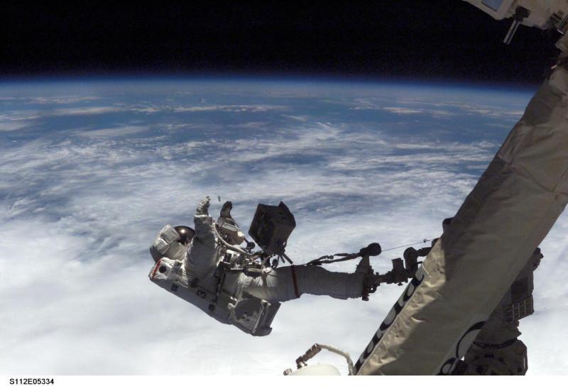 (12 октября 2002 года) - астронавт Дэвид А. Вольф, его ноги надежно закреплены в удерживающем устройстве на конце системы дистанционного манипулятора космической станции (SSRMS) или Canadarm2, кажется подвешенным над затянутой облаками частью Земли.