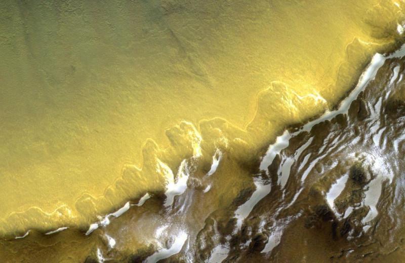 Снимок аппарата TGO российско-европейской миссии ExoMars2016 запечатлена юго-восточная стена 35-километрового кратера. На фото видны вечные залежи водяного льда.
