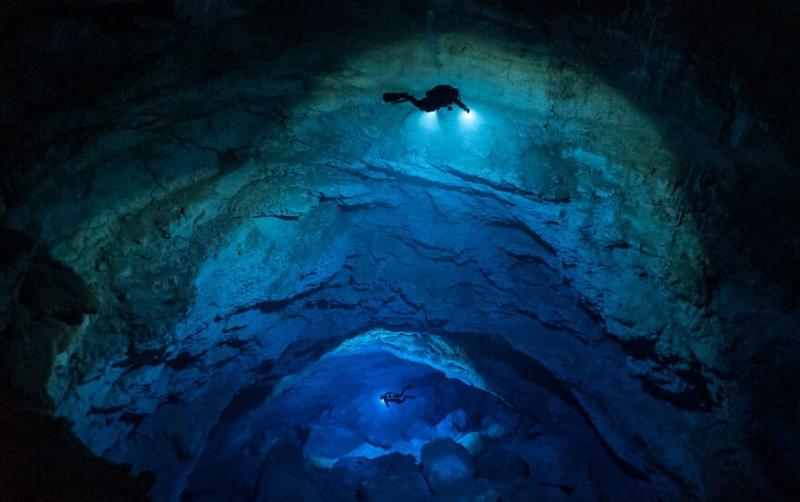 """Два технических дайвера спускаются в Голубую бездну Мексики. До этого места можно добраться на  подводном скутере и за 20 минут проплыть через неглубокую пещерную систему. """"Вы выскакиваете через дыру, и внезапно пол падает примерно на 70 метров"""", - говорит фотограф Си Джей Беннетт."""