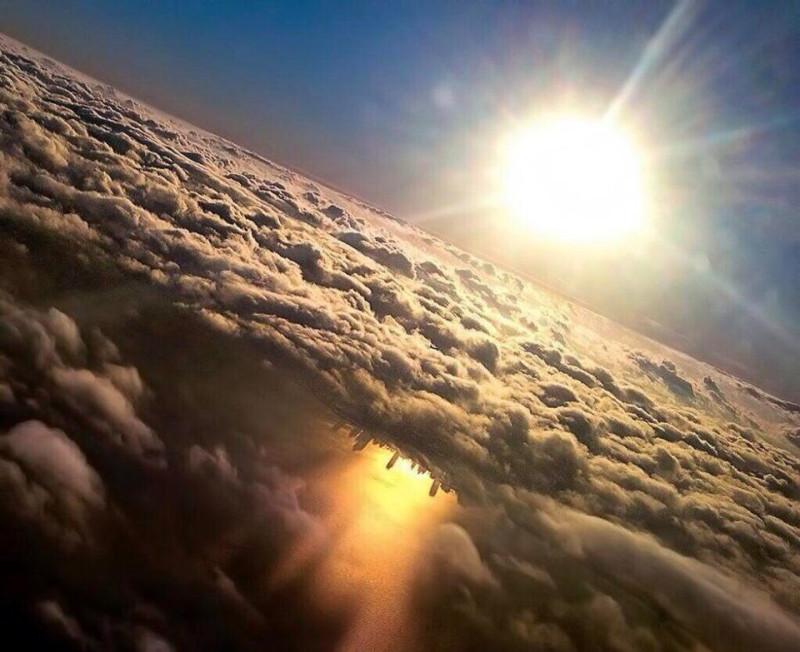 Фотограф-любитель Марк Херш запечатлел потрясающую сцену города, со своего места в самолете, направлявшемся в Чикаго и совершавшем свой последний заход на посадку. На послеполуденном снимке видно, как низкое солнце отбрасывает золотистый отблеск на воду, которая видна под покровом облаков.