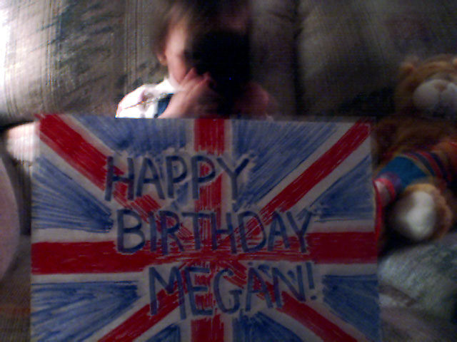 Laurel with a sign reading 'Happy Birthday Megan!' at her feet.
