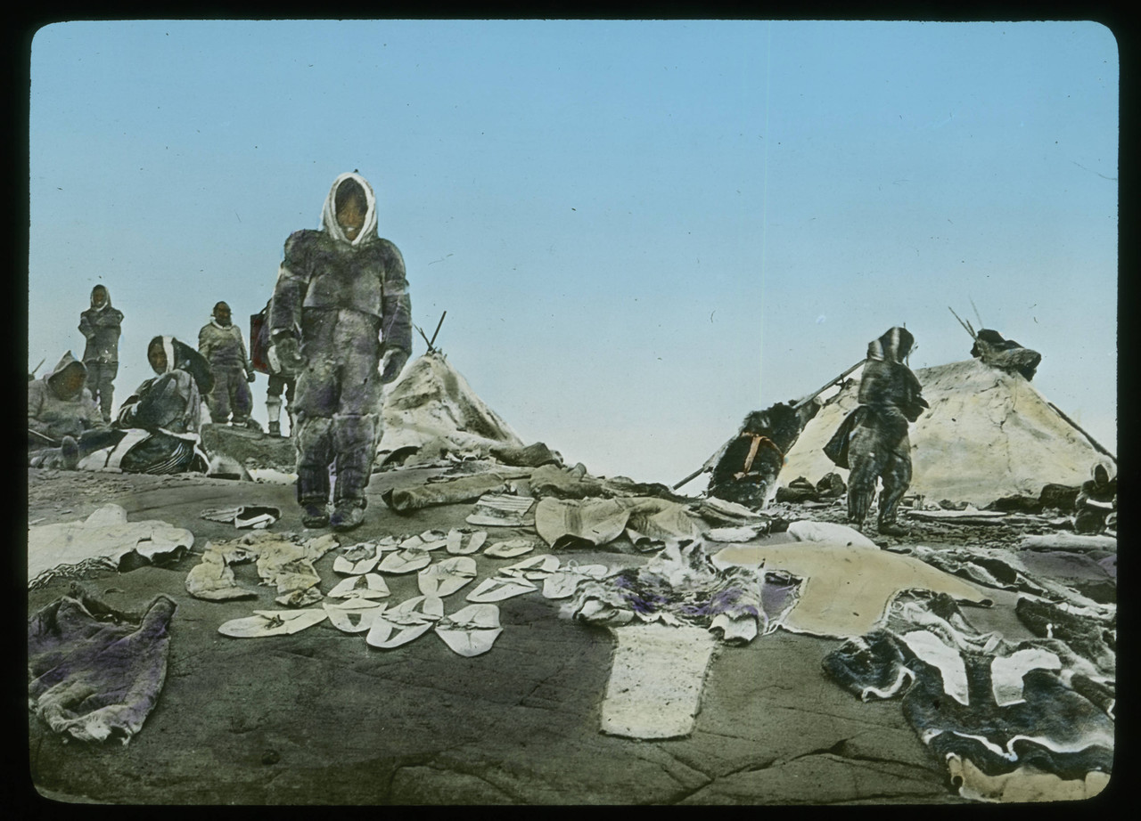 Handcolored_Indigenous_clothing_displayed_on_rocks_with_skin_covered_dwellings_in_the_background.jpg