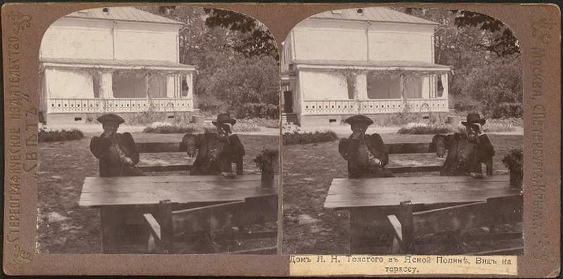 Ю.И.Игумнова и С.М.Прокудин-Горский за деревянным столом с букетом цветов около дома Л.Н.Толстого. Кулаков П.Е.