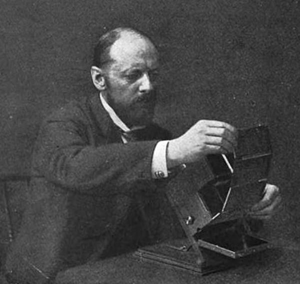 Ives inserting a Kromogram into a Junior Kromskop, circa 1899