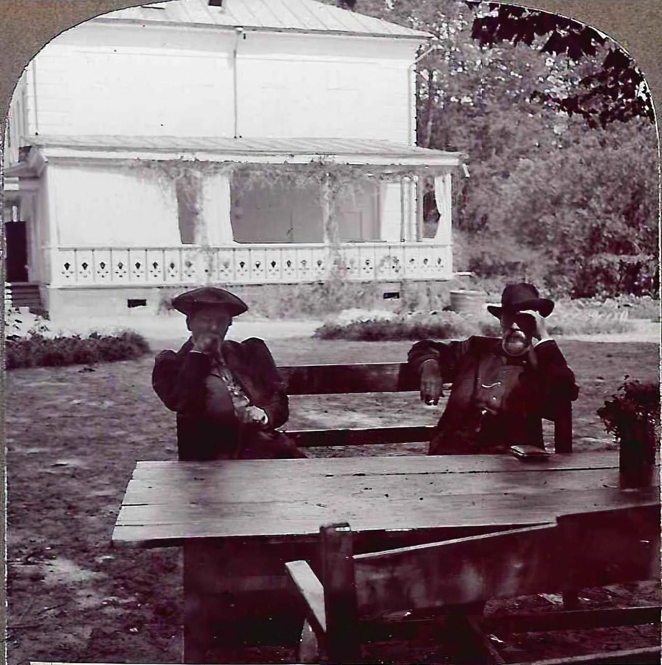 Ю.И.Игумнова и С.М.Прокудин-Горский за деревянным столом с букетом цветов около дома Л.Н.Толстого. Кулаков П.Е.4_cmpk
