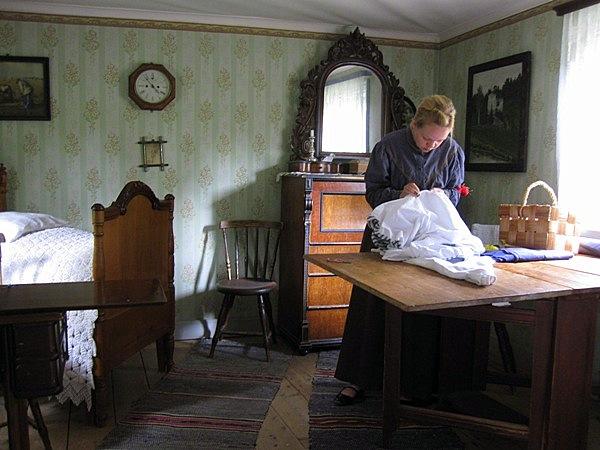 На переднем плане портниха шьет в интерьере финской комнаты середины ХХ века, а на заднем плане видно сложенную кровать