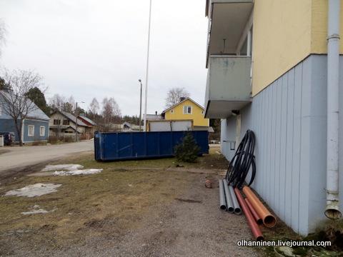 трубы и контейнер для мусора у дома