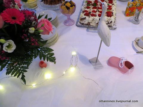 26 украшения в виде аиста и башмачков и цветы на столе с едой