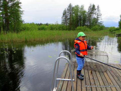 00 ребенок в жилете рыбачит на причале