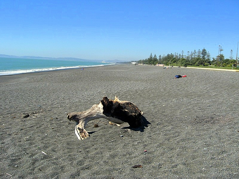 Безлюдный пляж с черным лавовым песком в Нейпире