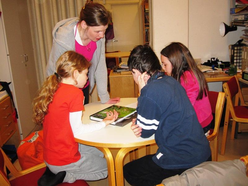 Учительница показывает группе детей из России книжку