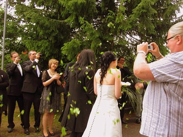 На фотографии видно, что вместо того, чтобы по традиции забрасывать жениха и невесту березовыми листьями