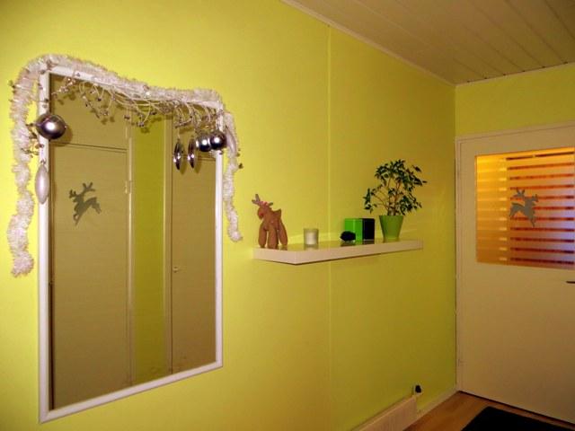 коридор, гирлянда и игрушки вокруг зеркала и олень на двери