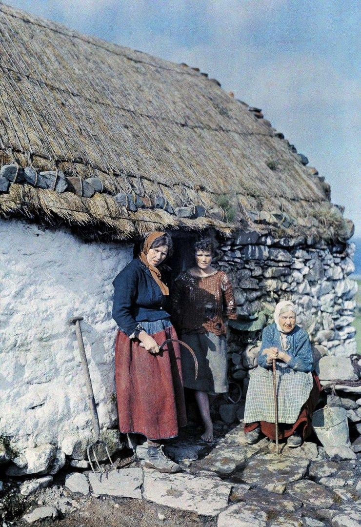 Три поколения женщин-крестьянок у каменного дома.