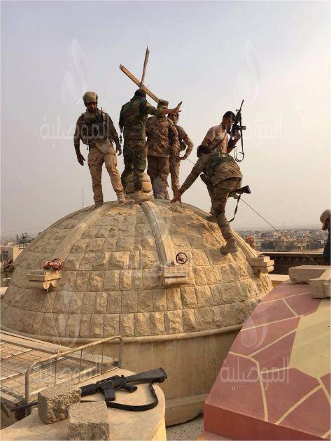 Солдаты Армии Ирака поднимают крест над куполом церкви в городе Карамалише около Мосула