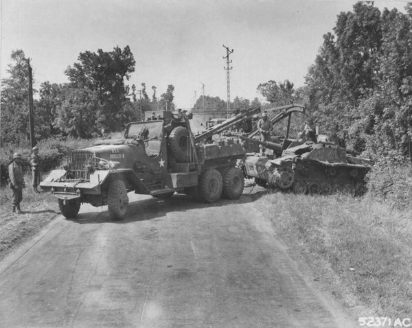Американский тягач эвакуирует брошенное немецкое штурмовое орудие StuG III