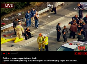 Screen shot of CNN clip - Police chase suspect down drain