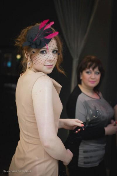 юная дев в беж платье и черн шляпке с перьями фуксия