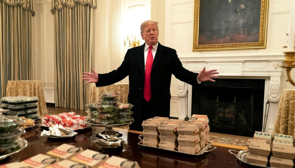 Президент Трамп в Белом доме у стола с десятками гамбургеров для приема футболистов команды Clemson Tigers, победителей национального студенческого чемпионата (январь 2019 года)