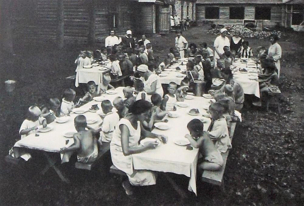 Воспитанники детского сада в летнем лагере во время обеда (1932 год)