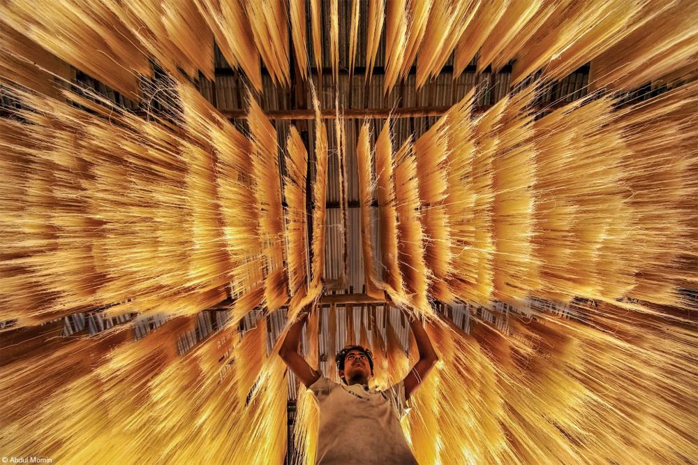 Рабочий проверяет, высохла ли рисовая лапша