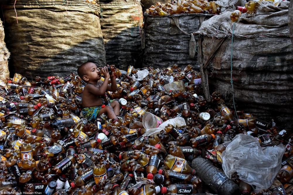 Маленький ребенок пьет из бутылки