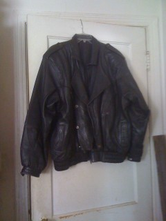 A black leather biking (?) jacket on a hanger hooked over the top of a white door.