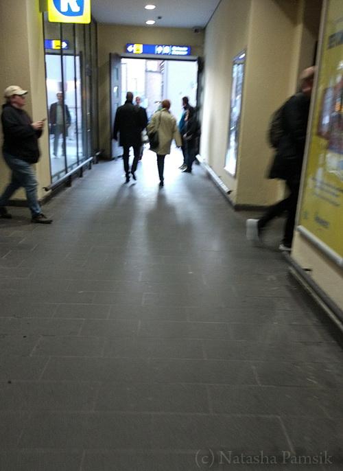 Вокзал. В белом плаще - она. Приехала в Хельсинке на пригородной электричке. Охранник несёт букет цветов в крафтовом кулёчке.