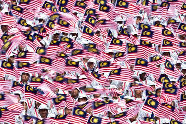 Malaysian schoolchildren wave national flags during the 57th National Day celebrations at Independence Square in Kuala Lumpur on August 31, 2014