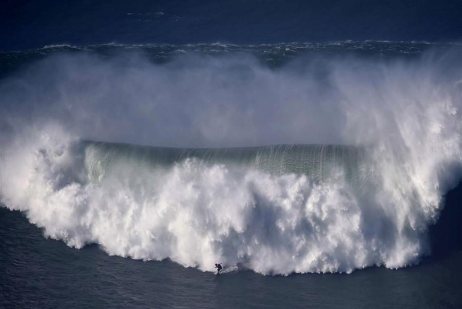 Surfer Praia do Norte in Nazare, central Portugal