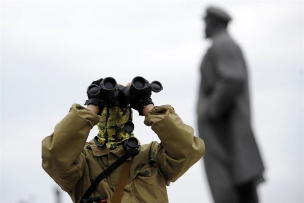 A pro-Russian militant looks through binoculars in front of the Statue of Lenin during a rally on Lenin Square in Donets