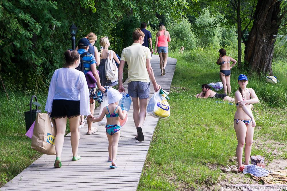 Люди идут с пляжа на Истринском водохранилище