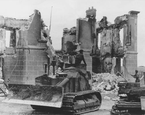 An armored Caterpillar D7 bulldozer from the Canadian Army Engineers demolishes ruined buildings in Normandy, France, after D-Day, circa July 1944.