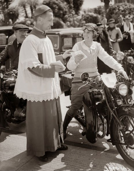 A reverend blesses the motorcycle of a woman who is learning to drive, 1938