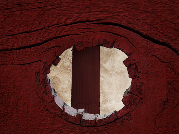 view of a door between stucco walls through a knothole in a fence